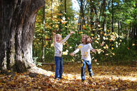 Kids throwing fall leaves in the air © Lisa Roberts