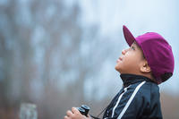Young boy holding binoculars while looking up at the sky