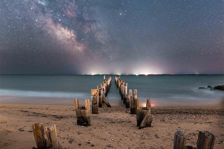 Starry sky and city lights on a beach in Falmouth © Evan Guarino