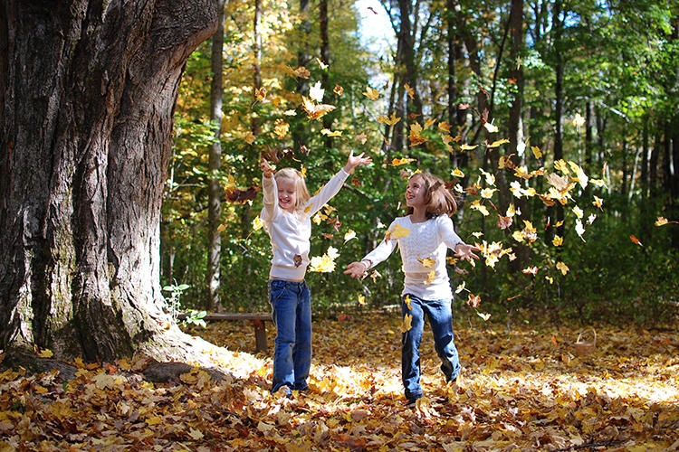Two young girls throwing fall leaves in the air © Lisa Roberts