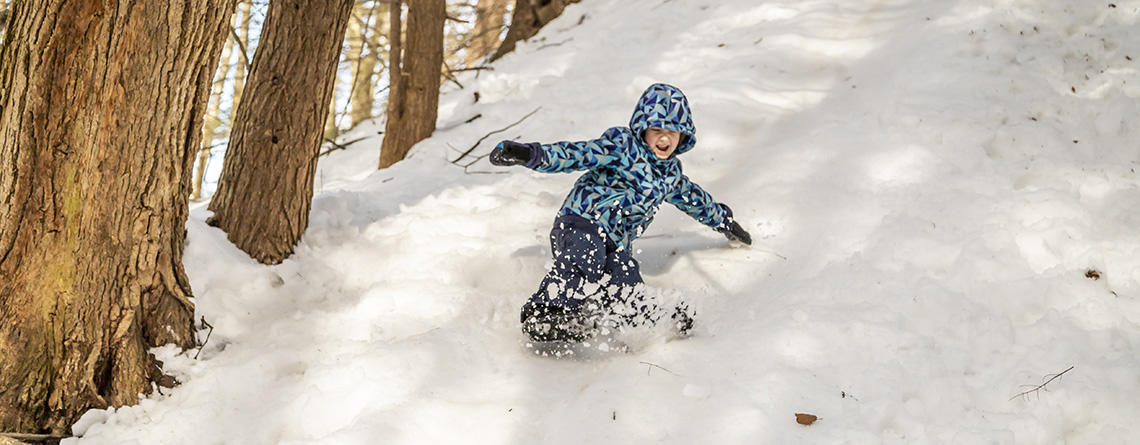 Boy in winter clothes sliding down a snowy hill at Arcadia Wildlife Sanctuary © Phil Doyle