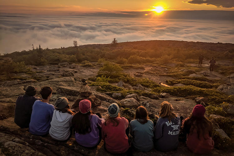 Group of teens watching sunrise from hiking summit